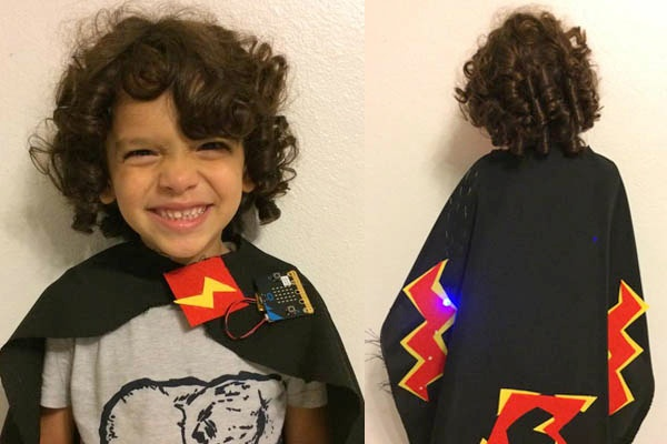Child wearing a cape with micro:bit at the collar