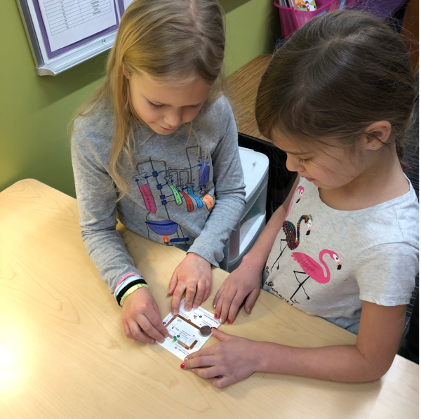 two second grade girls making a paper circuit