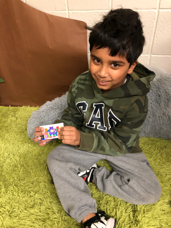 second grade boy showing off paper circuit