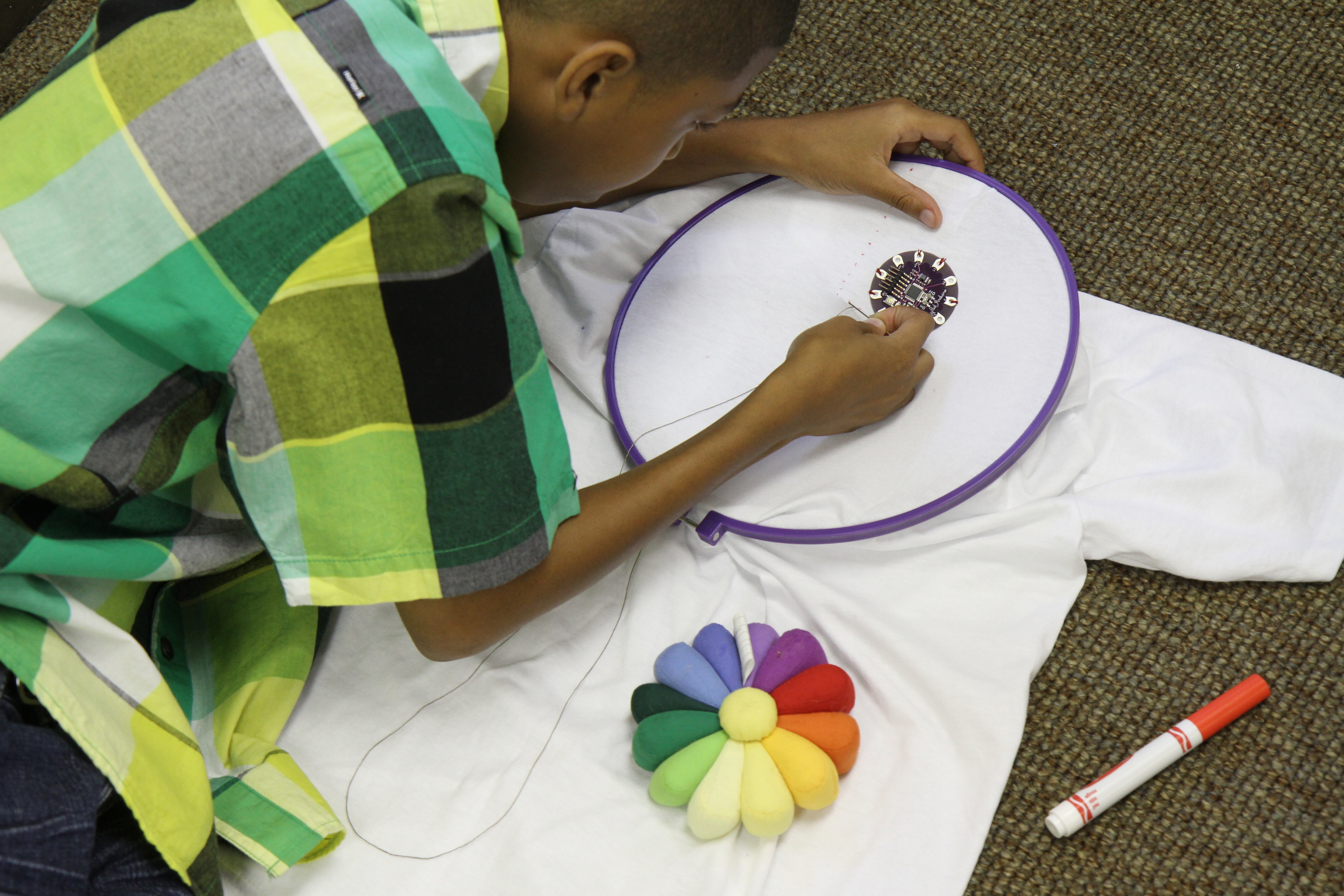 young boy sewing e-textiles with LilyPad