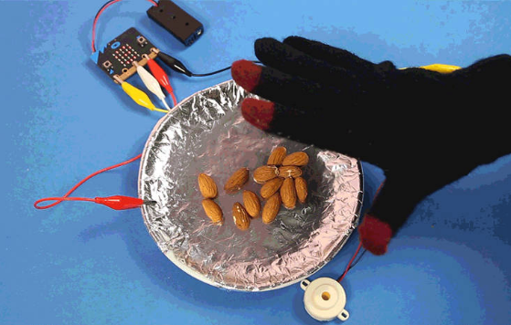 Electro Fingers glove connected to a micro:bit moving over a metal plate with almonds.