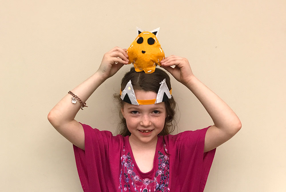 Camper wears an e-textile headband and holds a plush project above her