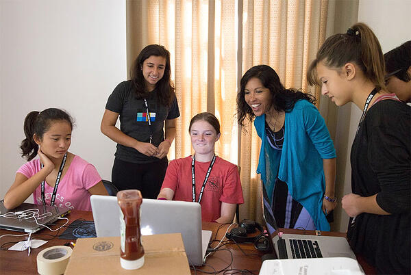 Made-by-Girls program graduate Uma B. teaching other students around a laptop