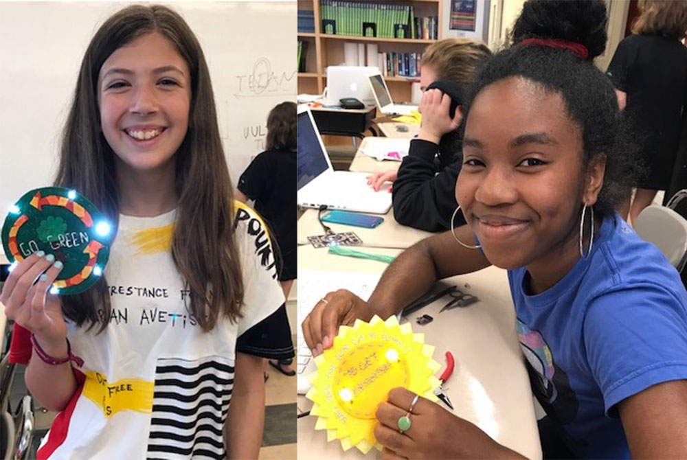 Two students holding light up e-textile badges they created.