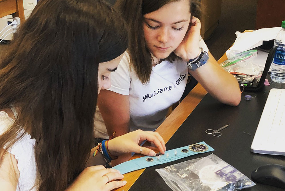 Two young women placing LilyPad components on a bracelet project